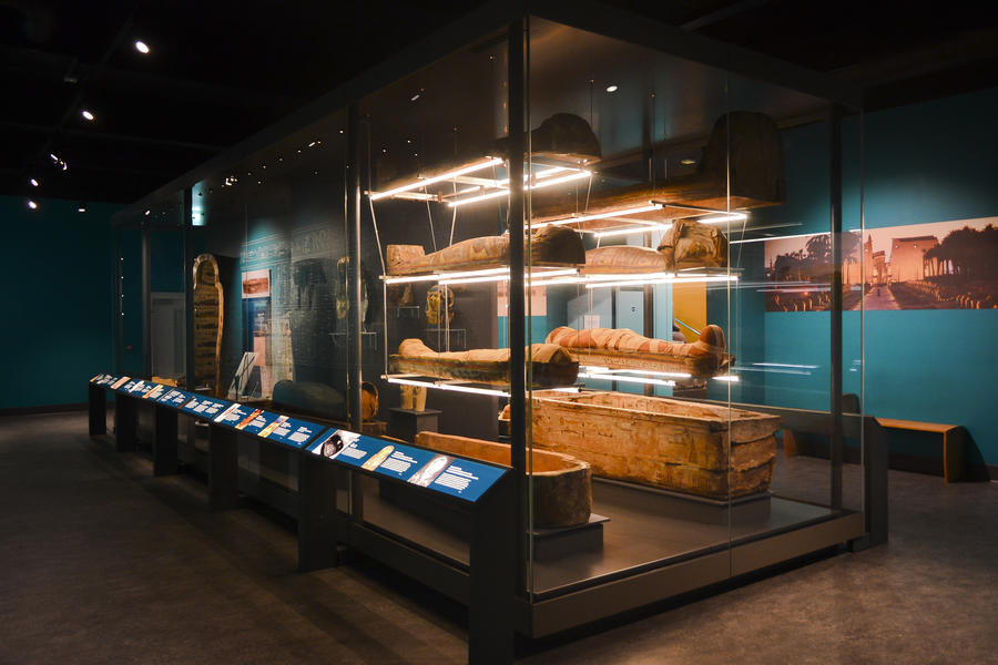 Large free-standing display case with mummies and sarcophagi